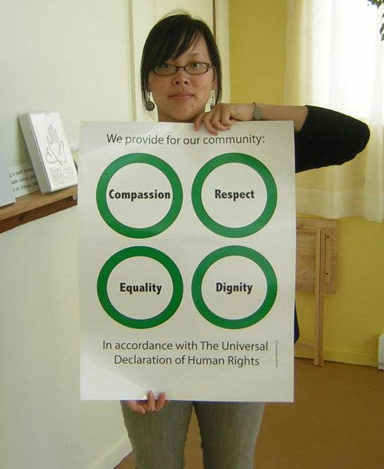Christina Chan is standing in the lobby of the Heart & Hands holding a poster with 4 green circles: Compassion, Respect, Equality, Dignity.