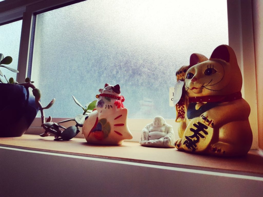 View of the bathroom windowsill with manekinekos and a jade plant.