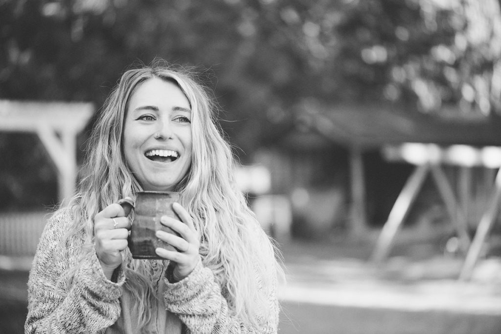 A black and white photo. C.M. has long hair, is standing outdoors, in a thick sweater, holding a mug in both hands.