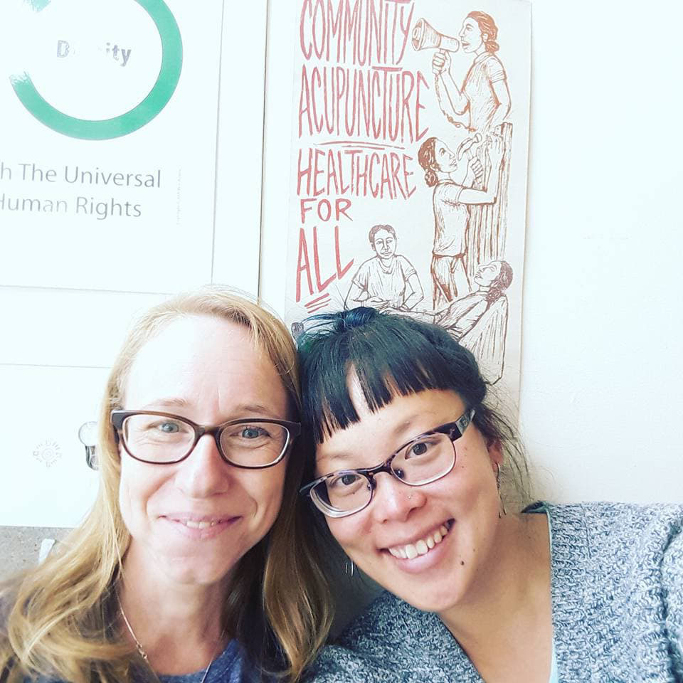 "M.G. is next to Christina Chan in the Heart & Hands lobby. Both of them wear glasses. In the background is a poster that says, ""Community Acupuncture Healthcare for All"""