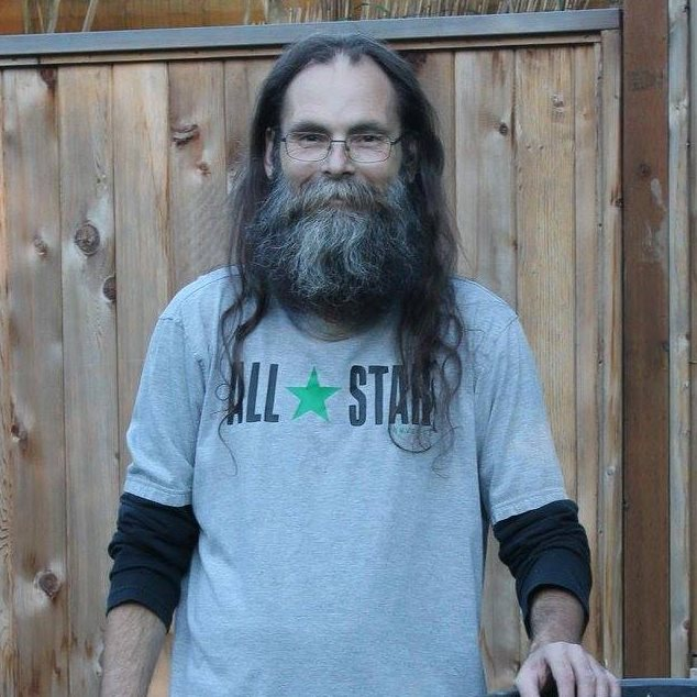 W.J.S. is standing in front of a wooden fence. He has long grey hair and beard, is wearing a grey t-shirt that says All Stars.