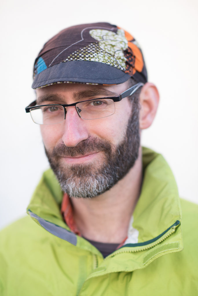 J.L has a dark, salt & pepper beard, glasses, wearing a cycling cap and a lime green jacket.