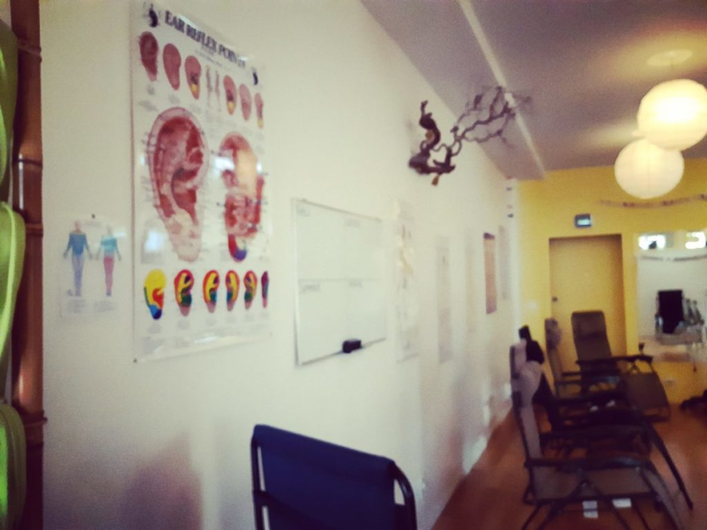 Entrance of the clinic room, auricular acupuncture poster, decorations, recliner chairs.