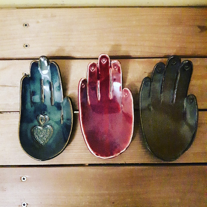 Three ceramic hands, red and green lined up in a row