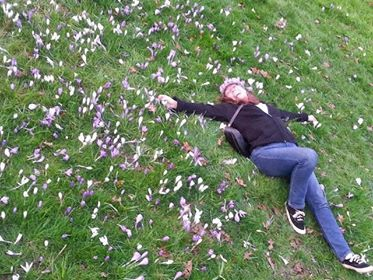 W.L. lying in the grass sprinkled with pink cherry blossoms. She is wearing jeans, black sweater, purse across her chest and a cap.