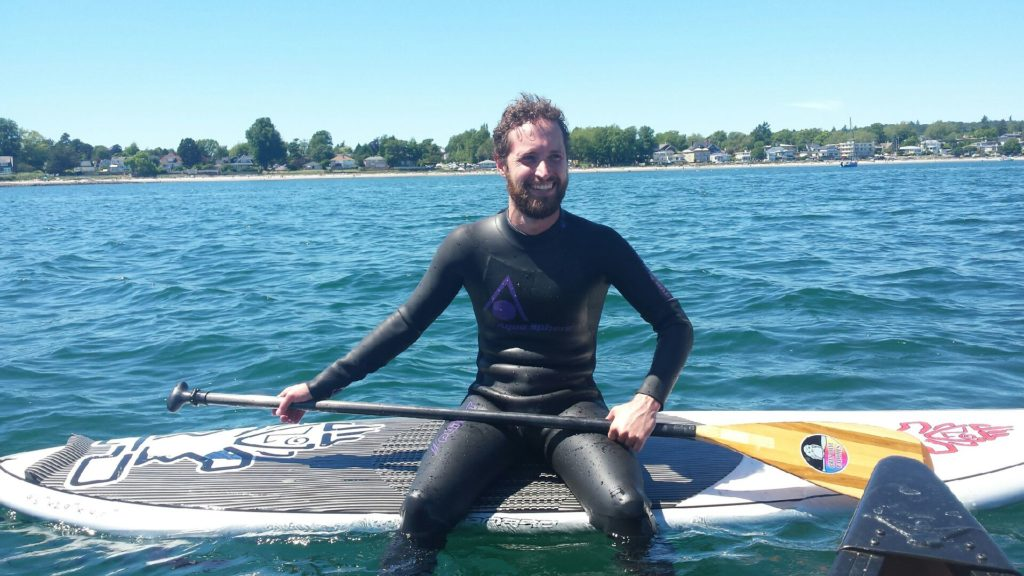 G.D. in a black wetsuit holding a paddle, sitting on a paddle board on open water