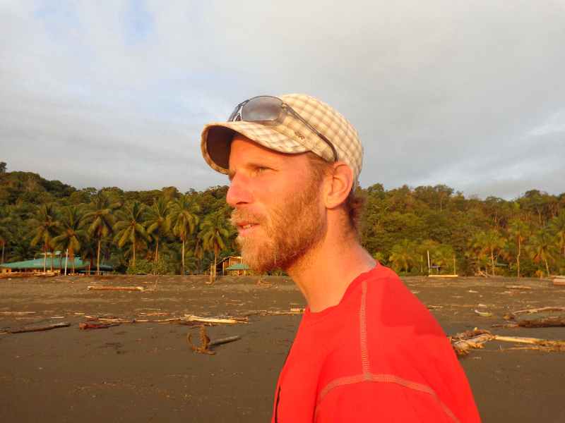 K.J. with a beard, somewhere tropical at sunset wearing a red t-shirt, tan cap and sunglasses.