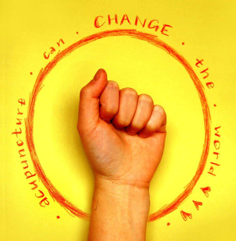Acupuncture can change the world in red on a yellow background with Christina Chan's fist in the foreground