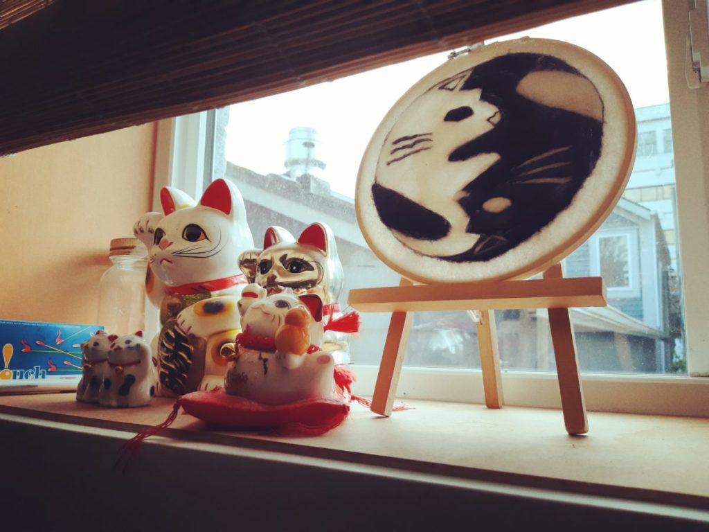 Ceramic manekineko on the kitchen windowsill.