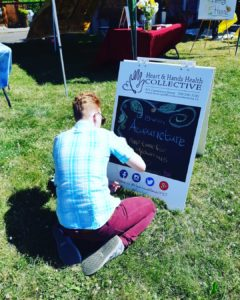 Quinn decorates our awesome sandwich board at FernFest 2018.