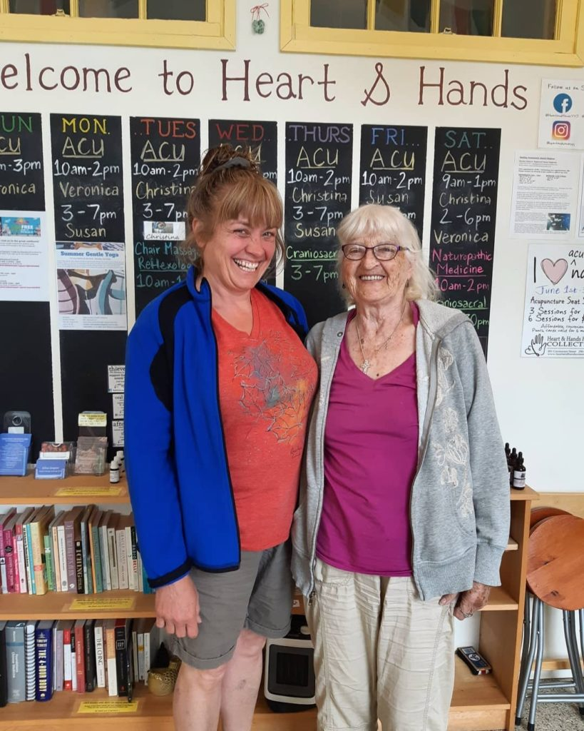 Collette Jobe and Millie Lacey standing in front of our weekly blackboard calendar in the lobby of Heart & Hands.