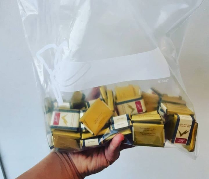 A ziploc bag of chocolates with gold foil wrappers