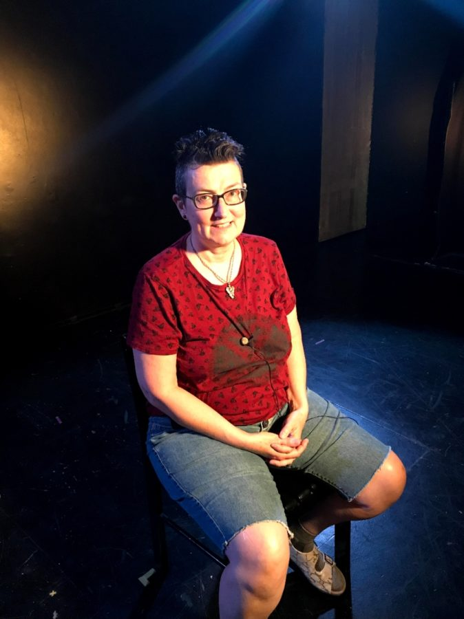 Tasha is wearing a red t-shirt, denim shorts sitting on a stool with stage lighting.