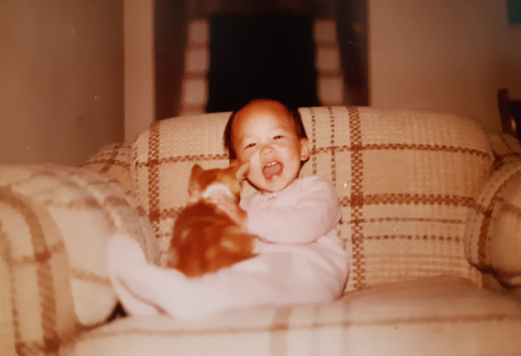 Christina in a pink onsie, on a plaid couch, holding an orange kitten