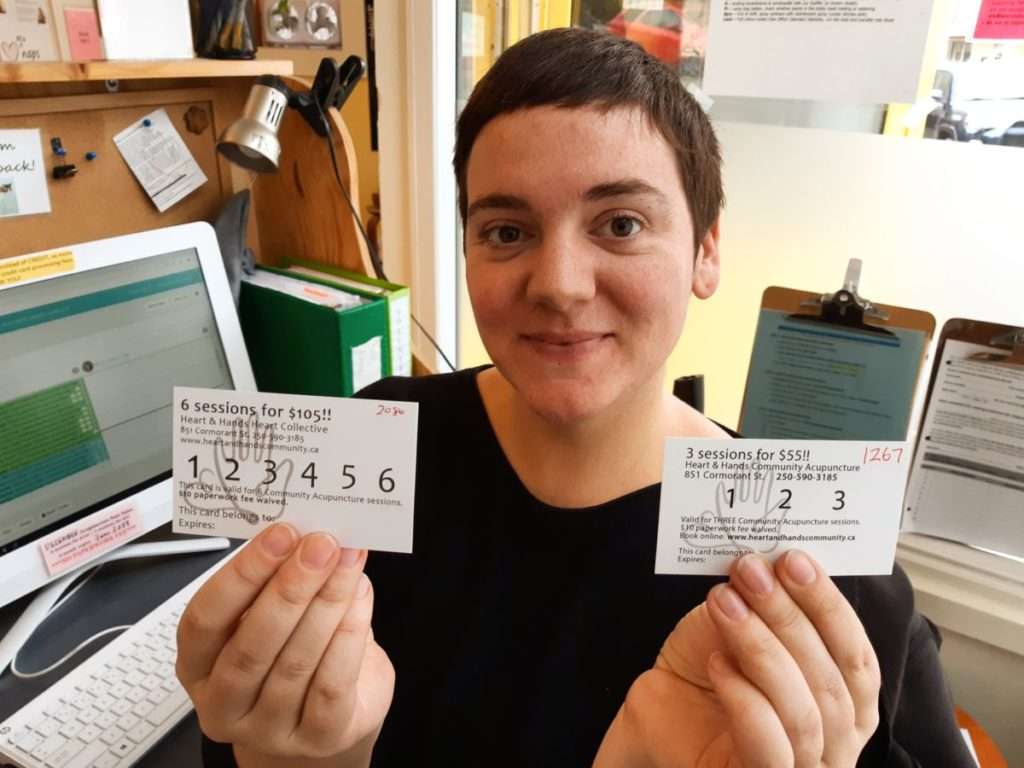 Bri sitting at the front desk holding 6 + 3 session punchcards