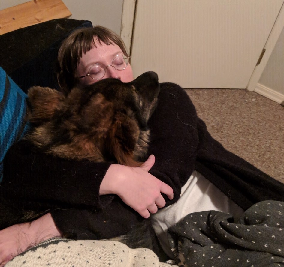 Arie is hugging her German Shepherd.