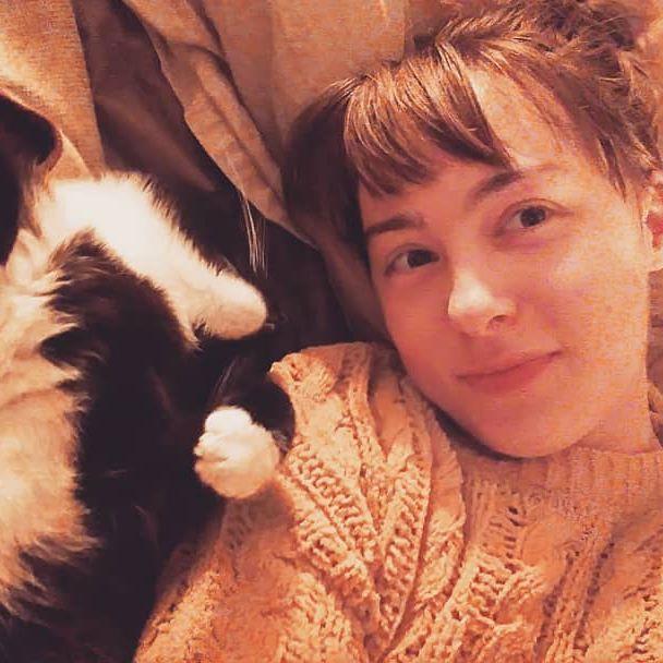 Xela selfie lying in bed with a B&W kitty