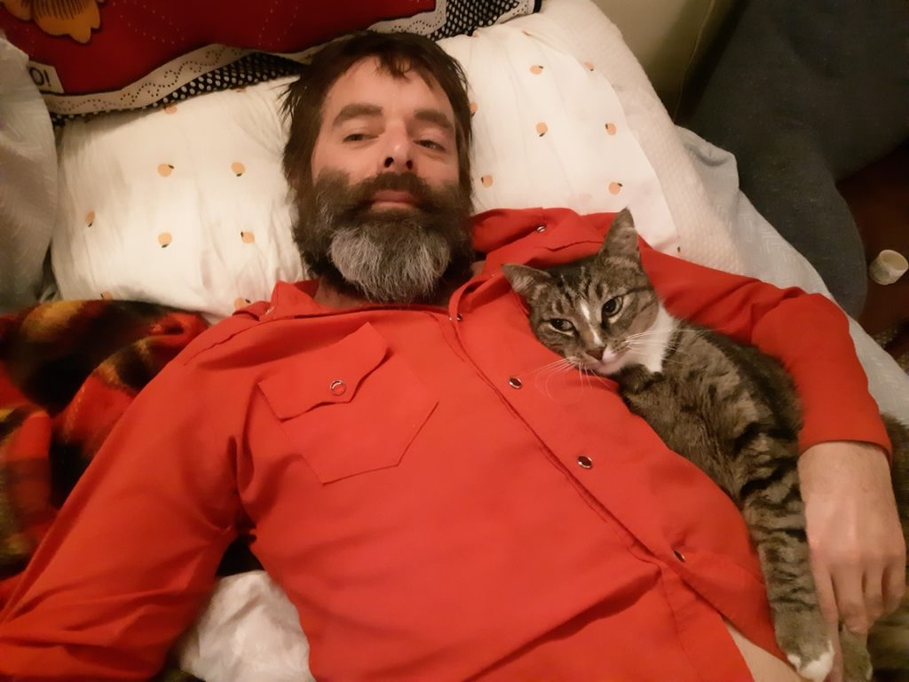 Denny has a beard, wearing a red shirt and his kitty