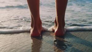 A young woman standing barefeet at the beach. Her feet are bathing in the waves that are rolling over the sand.