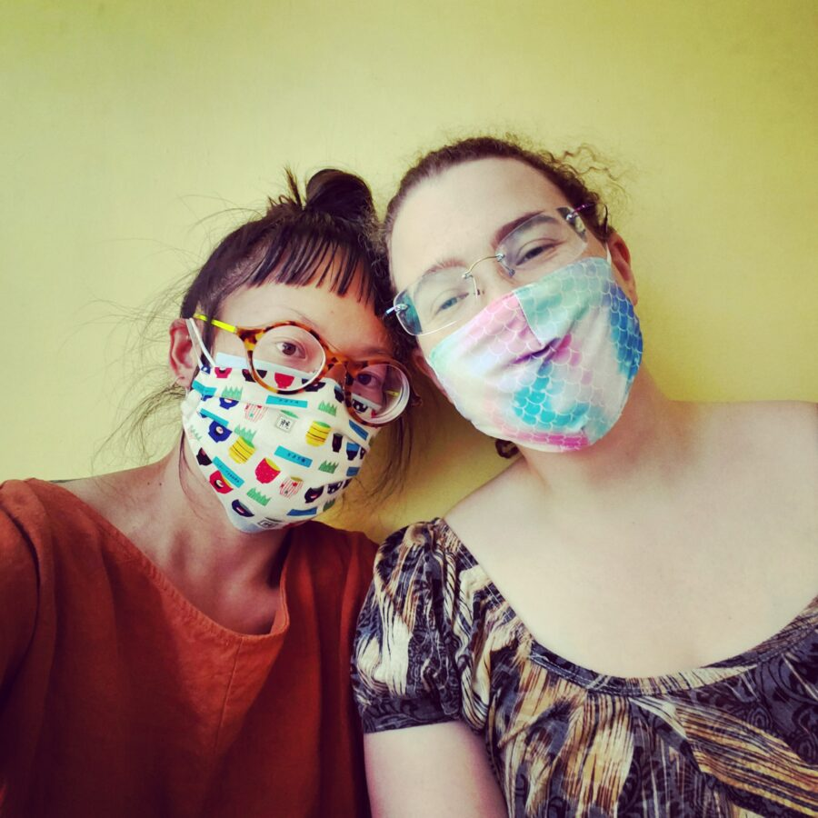 Christina is on the left and Brewster is on the right, both are wearing colourful masks
